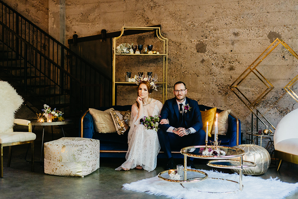 bride in an ivory lace gown with flowing sleeves and a braided hairstyle and the groom in a cobalt blue suit and a black long tie on the couch