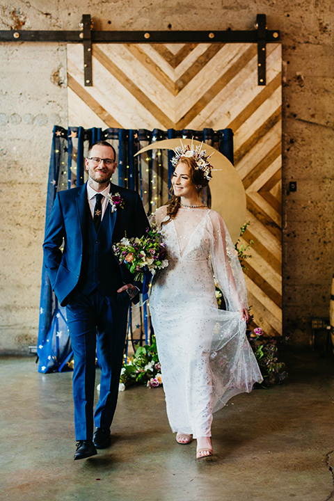 bride in an ivory lace gown with flowing sleeves and a braided hairstyle and the groom in a cobalt blue suit and a black long tie walking down the altar
