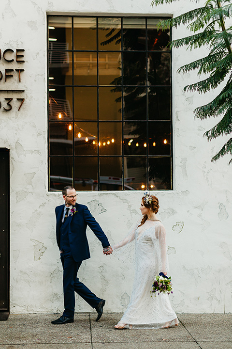 bride in an ivory lace gown with flowing sleeves and a braided hairstyle and the groom in a cobalt blue suit and a black long tie walking outside