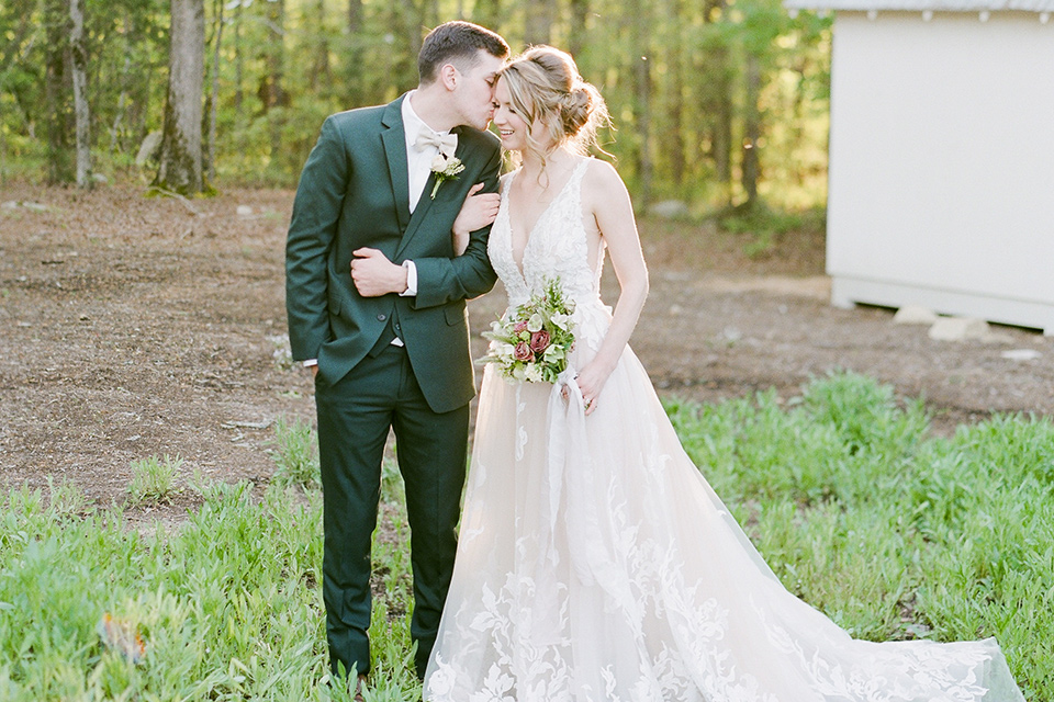 groom in a green suit with a platinum bow tie and the bride in a white lace gown