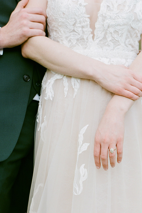 groom in a green suit with a grey bow tie and the bride in an ivory lace gown with an illusion neck line, close up