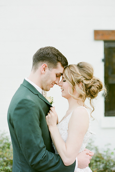 groom in a green suit with a grey bow tie and the bride in an ivory lace gown with an illusion neck line, embracing