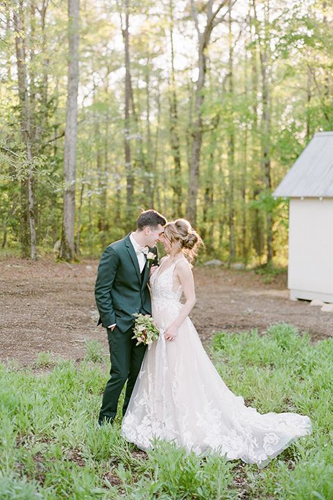 groom in a green suit with a grey bow tie and the bride in an ivory lace gown with an illusion neck line, touching heads