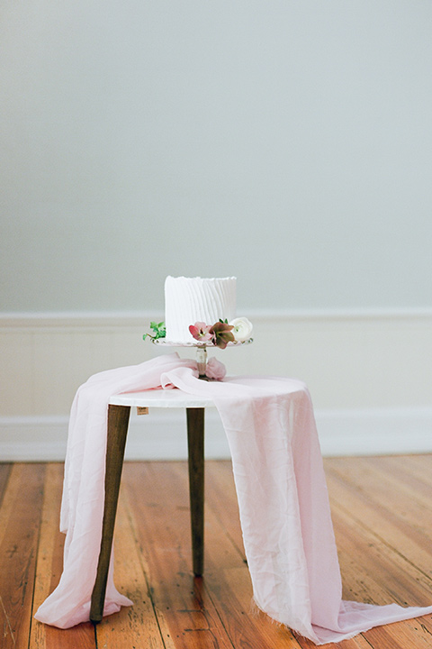 white cake on a table with a blush colored linen covered table