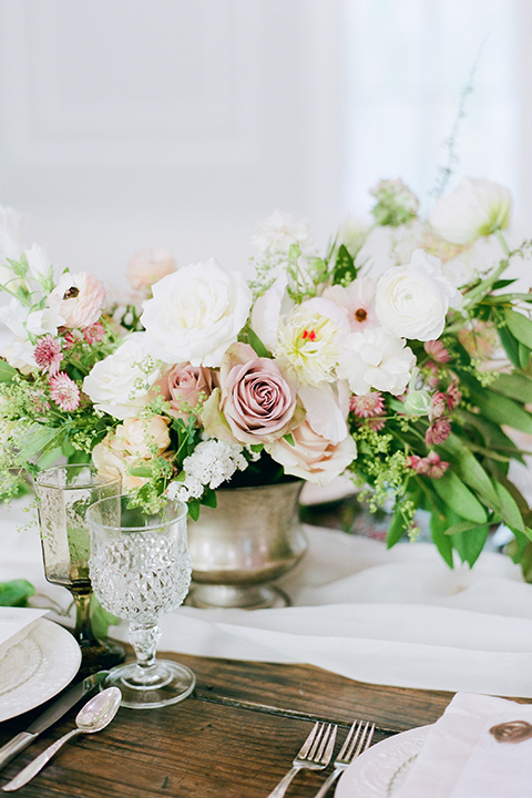 wooden table with white and blush flowers and silver flatware