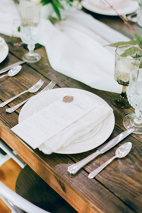 white plates and silver flatware on a wooden table