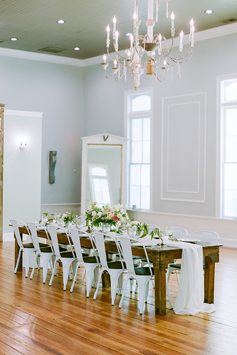 wooden table with white farm chairs and green + white floral centerpieces