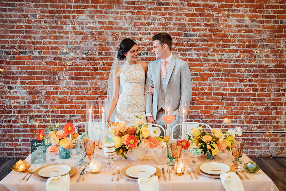 bride in a modern gown with a high neckline, no sleeves, and a tiered ruffled skirt and the groom in a light grey peak lapel suit with a coral long tie, by the sweetheart table