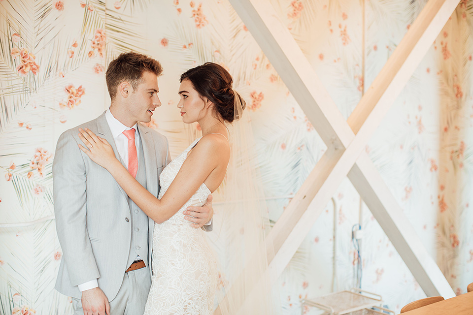bride in a modern gown with a high neckline, no sleeves, and a tiered ruffled skirt and the groom in a light grey peak lapel suit with a coral long tie, in room with windows