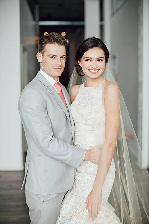 bride in a modern gown with a high neckline, no sleeves, and a tiered ruffled skirt and the groom in a light grey peak lapel suit with a coral long tie