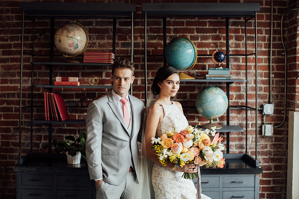 bride in a modern gown with a high neckline, no sleeves, and a tiered ruffled skirt and the groom in a light grey peak lapel suit with a coral long tie, in room with brick walls