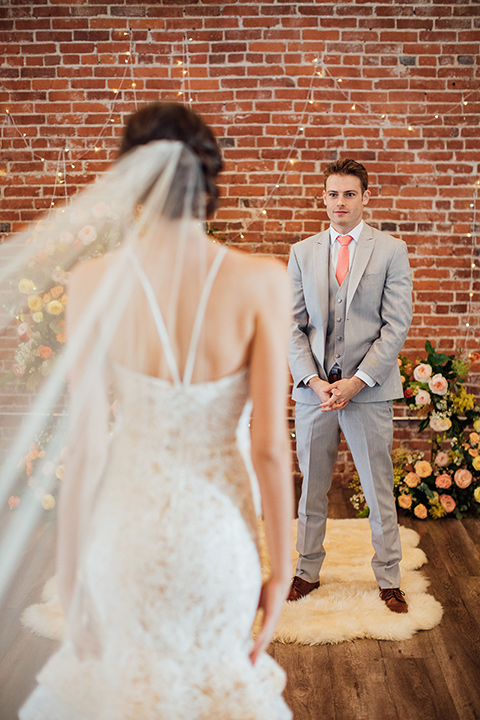 bride in a modern gown with a high neckline, no sleeves, and a tiered ruffled skirt and the groom in a light grey peak lapel suit with a coral long tie, at ceremony