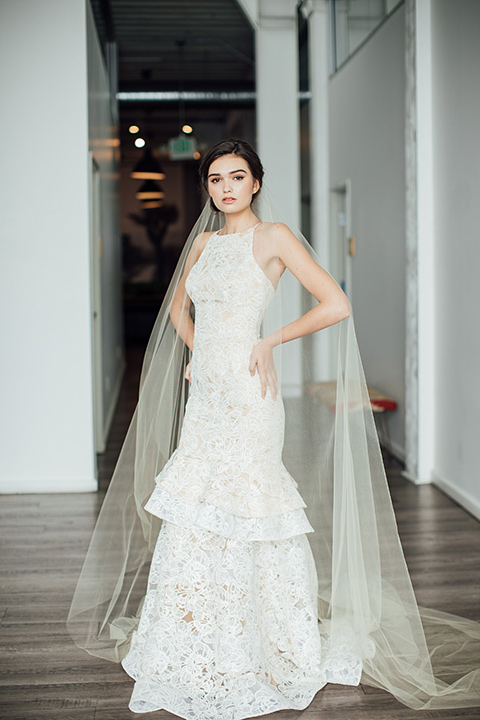 bride in a modern gown with a high neckline, no sleeves, and a tiered ruffled skirt