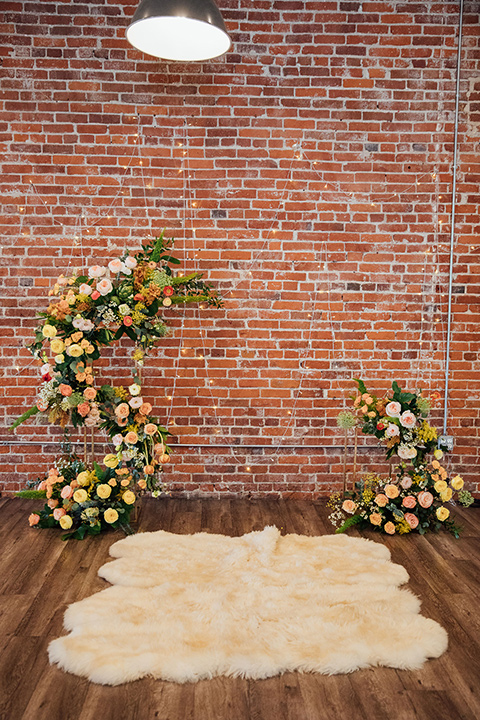 yellow and orange colored flowers on the ceremony arch