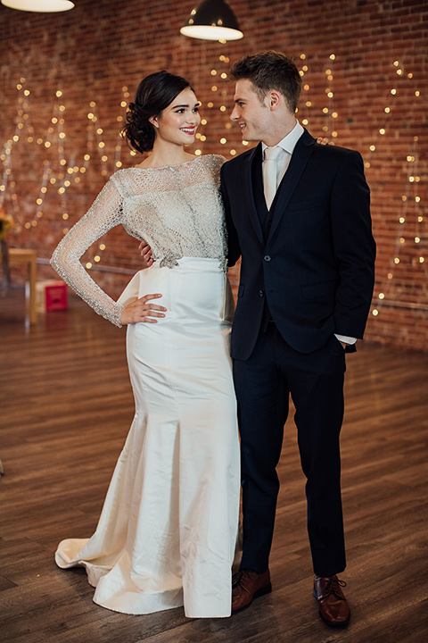 bride in a second gown with an illusion bodice and long sleeves with crystal detailing and a fitted skirt