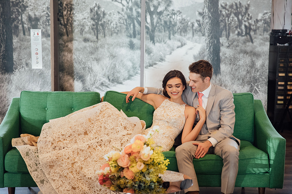 bride in a modern gown with a high neckline, no sleeves, and a tiered ruffled skirt and the groom in a light grey peak lapel suit with a coral long tie, in room gallery wall