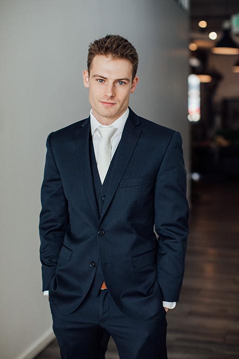 groom in a dark navy suit with a grey tie