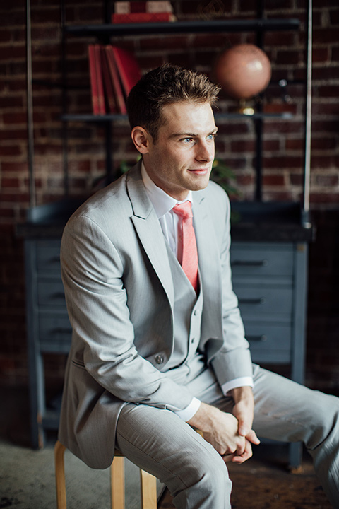 groom in a light grey suit with a coral tie