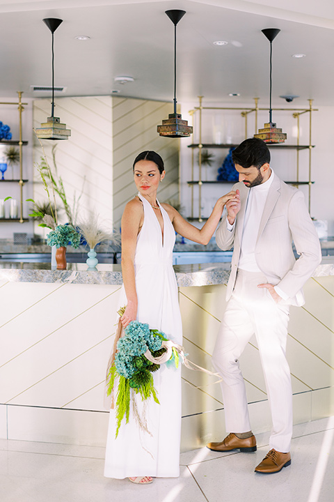 bride in a white jumpsuit with a halter and deep v neckline and her hair in a tight low bun and the groom in a light tan suit with a white shirt, next to the bar