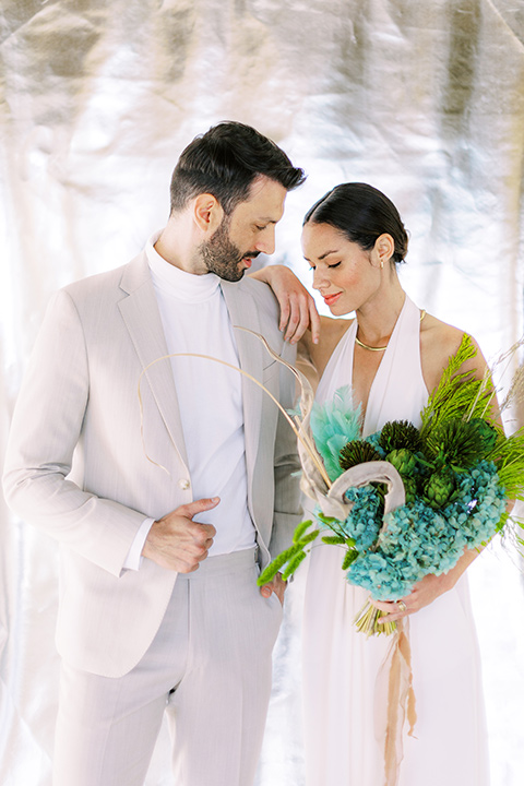 bride in a white jumpsuit with a halter and deep v neckline and her hair in a tight low bun and the groom in a light tan suit with a white shirt, at ceremony space