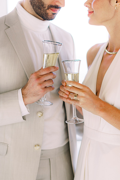 bride in a white jumpsuit with a halter and deep v neckline and her hair in a tight low bun and the groom in a light tan suit with a white shirt, cheersing with champagne