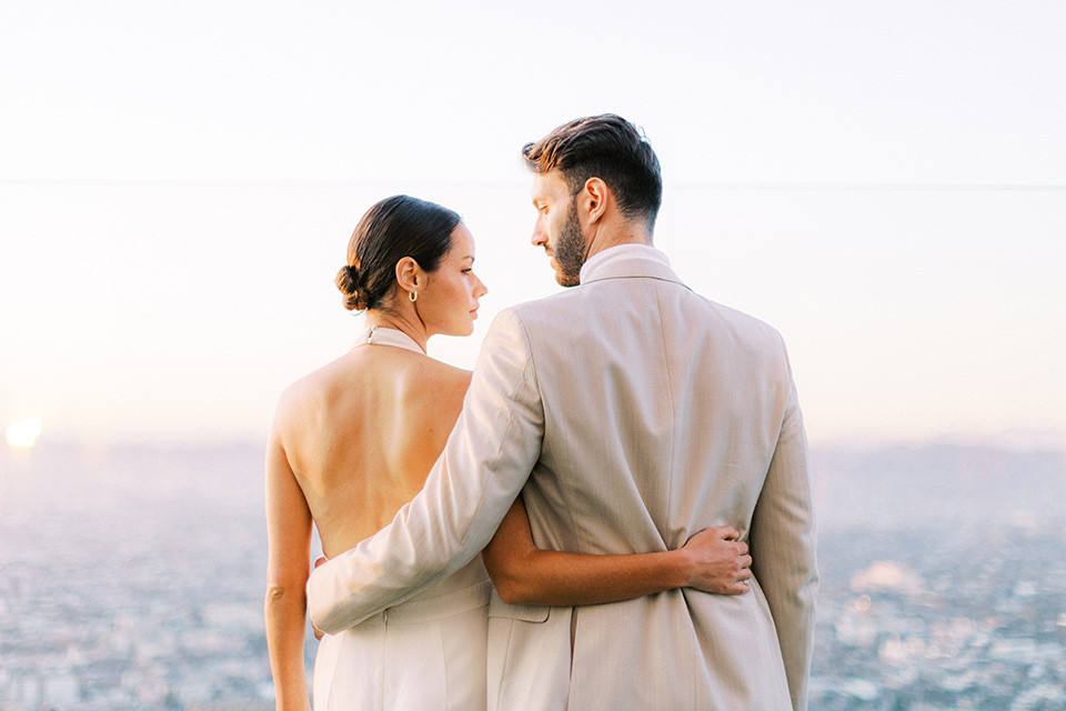 bride in a white jumpsuit with a halter and deep v neckline and her hair in a tight low bun with the city behind them