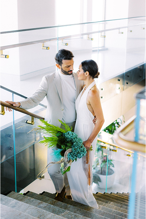 bride in a white jumpsuit with a halter and deep v neckline and her hair in a tight low bun and the groom in a light tan suit with a white shirt walking down the stairs
