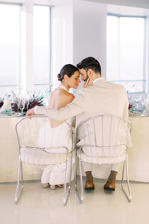 bride in a white jumpsuit with a halter and deep v neckline and her hair in a tight low bun and the groom in a light tan suit with a white shirt sitting at the reception