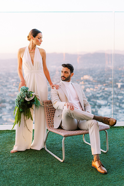 bride in a white jumpsuit with a halter and deep v neckline and her hair in a tight low bun and the groom in a light tan suit with a white shirt sitting out on the rooftop with the city behind them