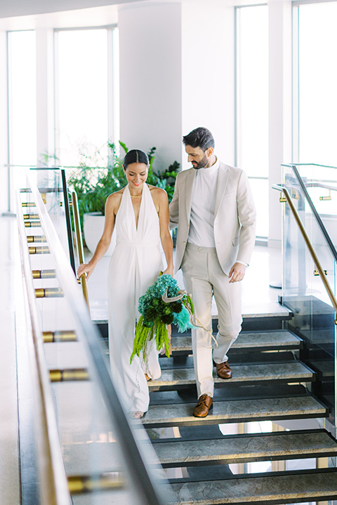 bride in a white jumpsuit with a halter and deep v neckline and her hair in a tight low bun and the groom in a light tan suit with a white shirt, heading down the stairs