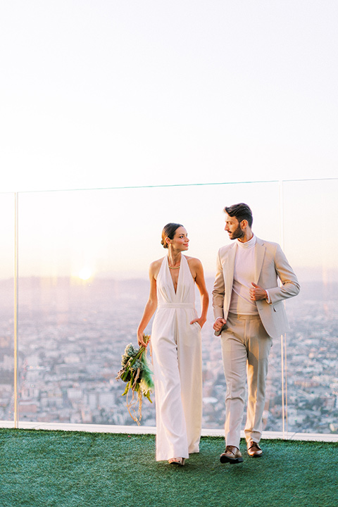 bride in a white jumpsuit with a halter and deep v neckline and her hair in a tight low bun and the groom in a light tan suit with a white shirt walking outside with the city behind them