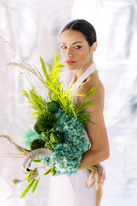 bride in a white jumpsuit with a halter and deep v neckline and her hair in a tight low bun, and carrying a blue and green floral bouquet