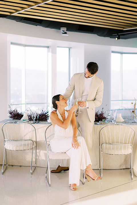 bride in a white jumpsuit with a halter and deep v neckline and her hair in a tight low bun and the groom in a light tan suit with a white shirt sitting at the reception table