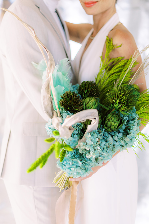 bride in a white jumpsuit with a halter and deep v neckline and her hair in a tight low bun and the groom in a light tan suit with a white shirt, close up on tropical style florals