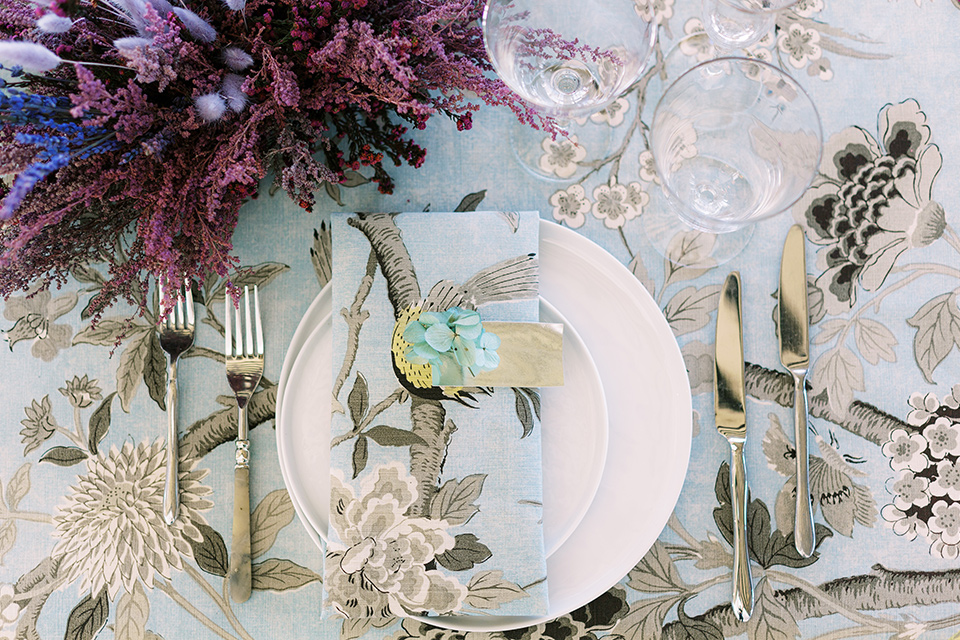 silver and blue floral tablecloth with white plates and silver flatware