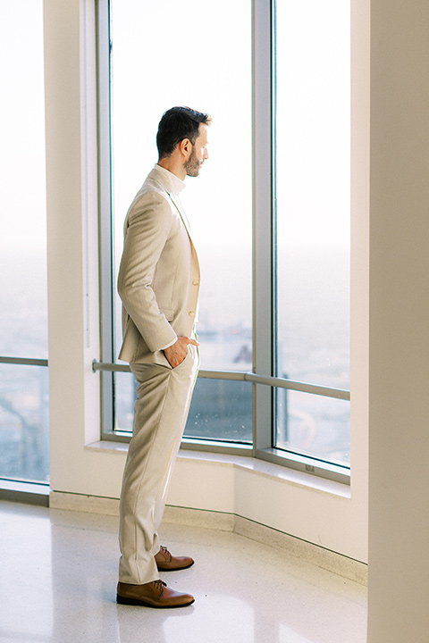 the groom in a light tan suit with a white shirt looking out the window
