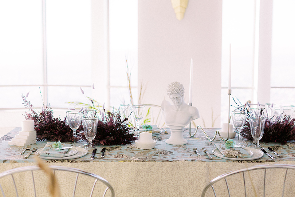 silver and blue floral tablecloth with white plates and silver flatware in front of windows overlooking the city