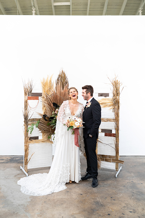 the bride in a lace white gown with long sleeves and a flowing skirt with hair in a modern low bun and the groom in a black suit with a long black tie next to the ceremony decor