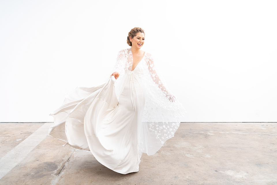 the bride in a lace white gown with long sleeves and a flowing skirt with hair in a modern low bun
