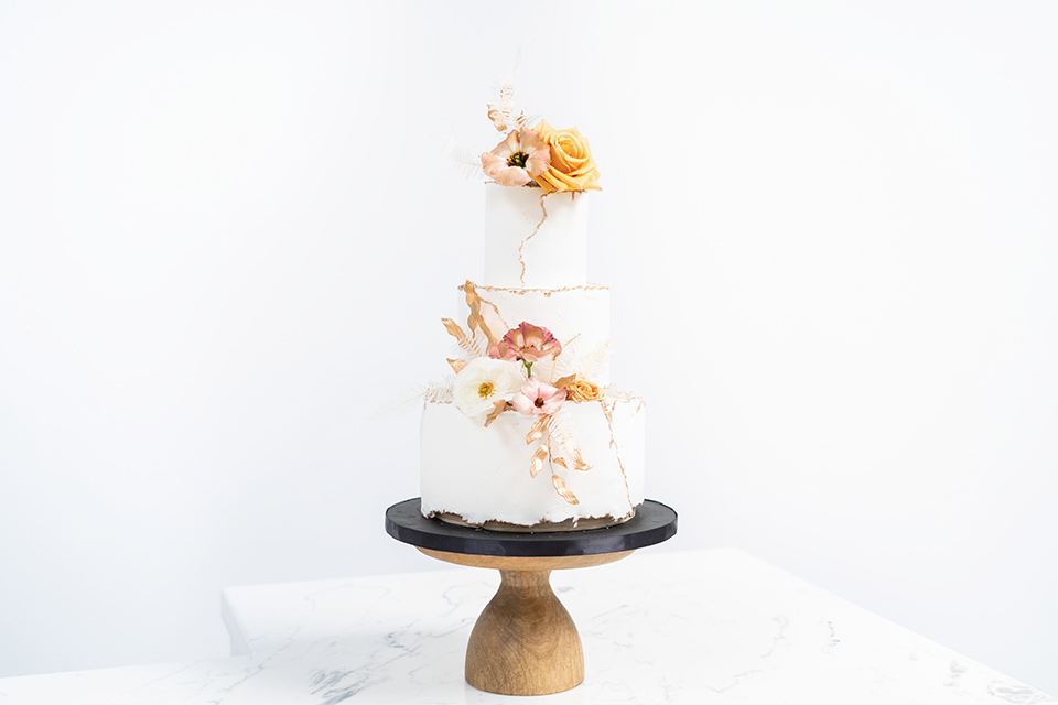 white cake with gold and neutral details