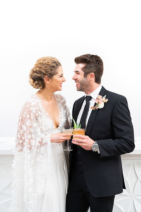 the bride in a lace white gown with long sleeves and a flowing skirt with hair in a modern low bun and the groom in a black suit with a long black tie with drinks