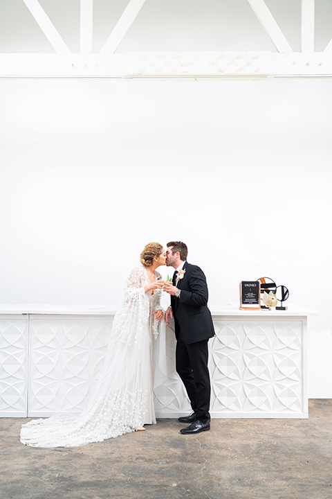 the bride in a lace white gown with long sleeves and a flowing skirt with hair in a modern low bun and the groom in a black suit with a long black tie