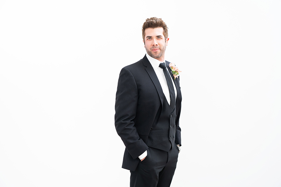 the groom in a black suit with a long black tie