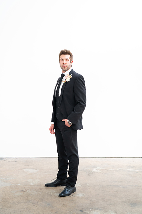 groom in a black suit with a black long tie