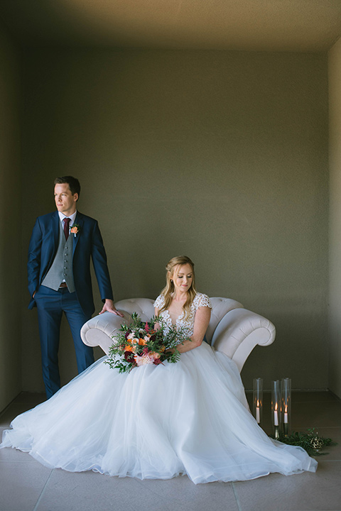 the bride in a flowing a line gown with a lace bodice in a low cut neckline and the groom in a dark blue suit with a grey vest and burgundy long tie