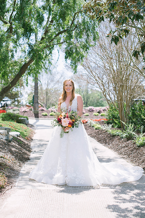 the bride in a flowing a line gown with a lace bodice in a low cut neckline