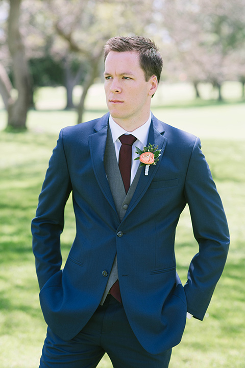 the groom in a dark blue suit with a grey vest and burgundy long tie