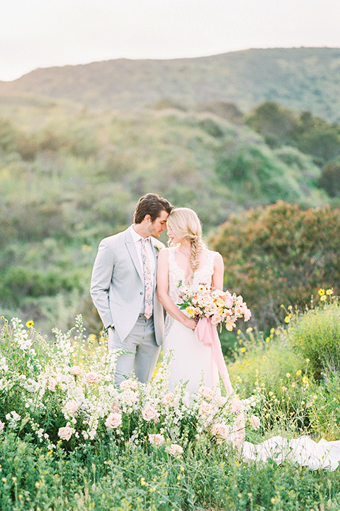 bride in a French inspired casual flowing gown and the groom in a light grey peak lapel suit