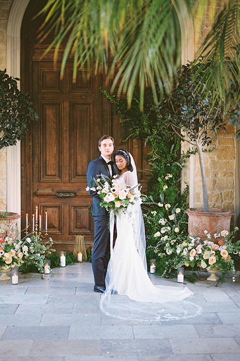 couple at ceremony groom in a navy blue tuxedo with a black bow tie and the bride in a white lace flowing gown and a long cathedral veil