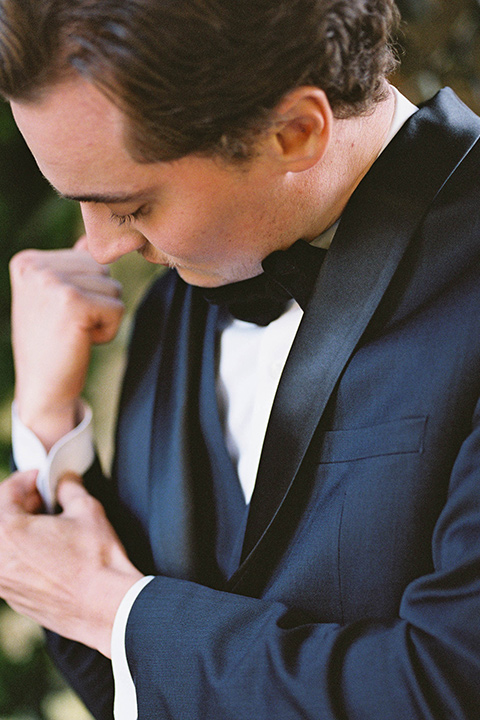groom in a navy blue tuxedo with a black bow tie